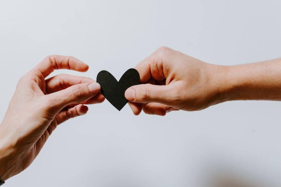 Dwie dłonie trzymające czarne serce