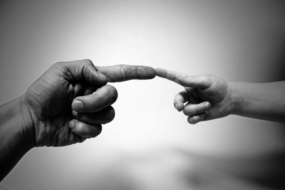 Dwie dłonie stykające się ze soba placami wskazującymi